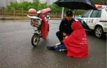 济南一市民骑车不慎摔伤 民警雨中为其撑伞挡风