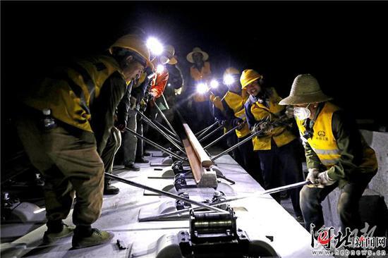 6月11日,施工人员在崇礼铁路太子城隧道进行最后一对区间轨道铺设。