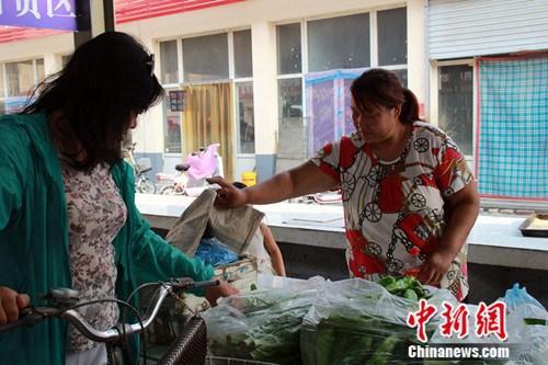 """定州""""三轮姐""""胡会甫变身""""卖菜姐""""。图为胡会甫为顾客挑选蔬菜。 于俊亮 摄"""