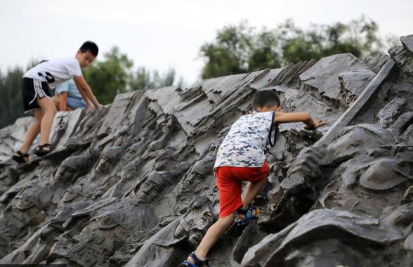沈阳故宫广场浮雕成攀爬墙 攀爬者以儿童居多
