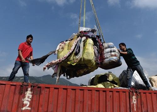 """资料图:在深圳海关开展的一次""""洋垃圾""""销毁行动中,工作人员在搬运走私废旧衣物。(马来西亚《星洲日报》网站)"""