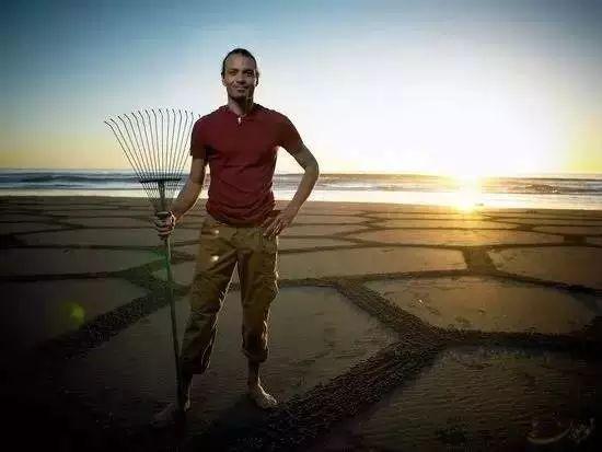 他用一把耙子在海滩画画