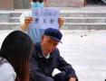 """名震杭州的84岁""""假摔帝""""再现江湖 网友默默在旁举牌提醒勿上当"""