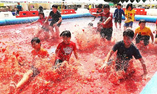 韩国西红柿节 儿童红色海洋中嬉戏玩耍